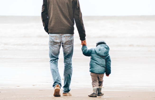 Child Holding Father's hand walking on beach